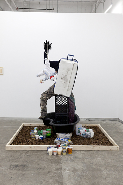 Wood, plastic, pine bark, landscaping pond, cups, pump, hose, rocks, bricks, mil-crates, trousers, boot, coller, duct tape, beer can, costume hand, electric cord, babydoll, stuffed bear, bobber and water<br>70 X 85 X 90 INCHES
